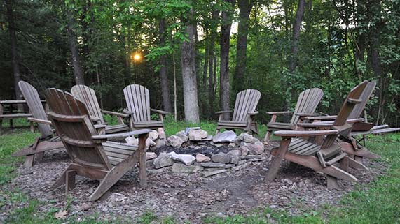 Wooden chairs around a fire pit